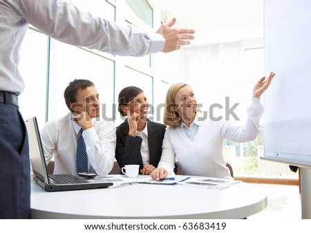Image of businesspeople pointing at board during presentation