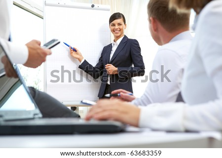 Image of businesswoman doing presentation to businesspeople during conference
