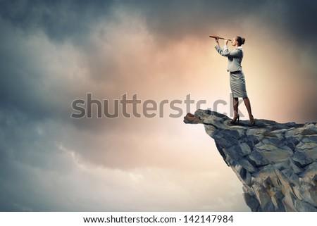 Image of businesswoman looking in telescope standing a top of rock