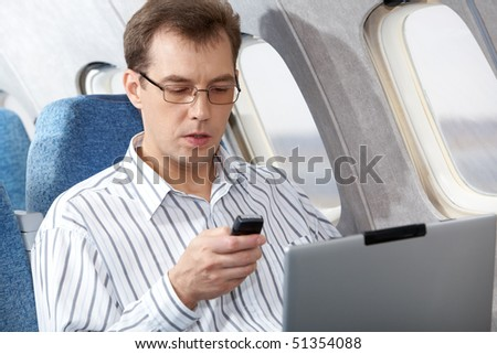 Image of busy businessman working during flight