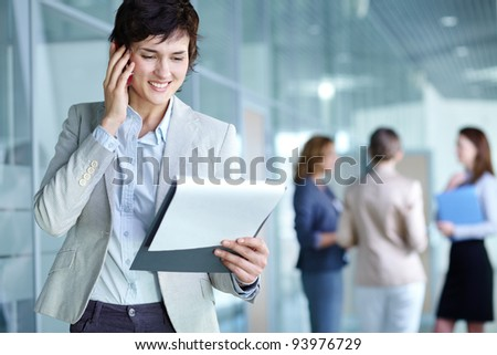 Image of busy female calling on the phone and reading document in working environment