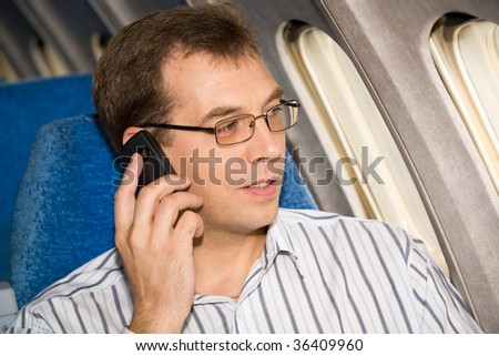 Image of busy male in sunglasses speaking by the mobile phone during flight