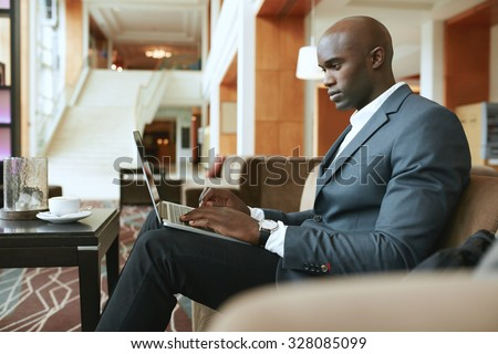 Image of busy young businessman working on laptop. African businessman sitting in hotel lobby waiting for someone.