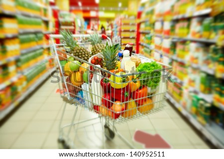 Image of cart full of products in supermarket