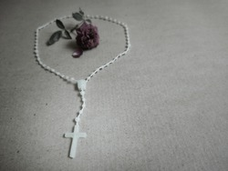 image of Catholic string beads or rosary beads with rose on paper background