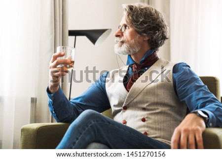 Image of caucasian adult professor man wearing stylish suit and eyeglasses drinking alcohol from glass while sitting on armchair in hotel apartment
