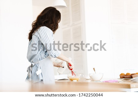 Image of caucasian brunette woman wearing apron preparing dough while cooking pie in modern kitchen stock photo