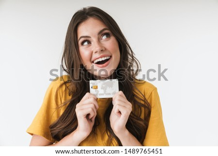 Image of caucasian brunette woman wearing casual clothes smiling and holding credit card isolated over white background