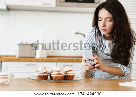 Image of caucasian concentrated woman wearing apron taking photo muffins on cellphone in modern kitchen stock photo