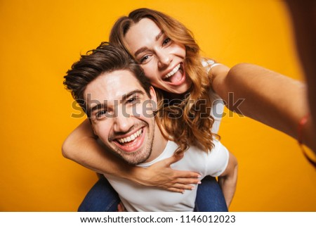 Image of caucasian couple having fun and taking selfie while man piggybacking cute young woman isolated over yellow background #1146012023