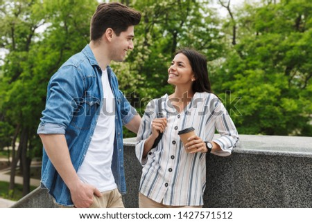 Image of caucasian couple man and woman with paper cup smiling and talking while standing on stairs outdoors