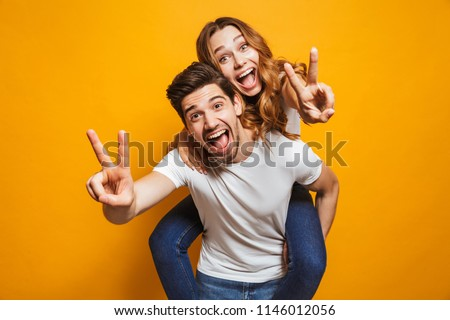 Image of caucasian man having fun and giving piggyback ride to joyful woman isolated over yellow background