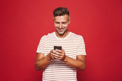 Image of caucasian man in striped t-shirt smiling and holding mobile phone isolated over red background