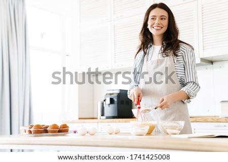 Image of caucasian smiling woman wearing apron preparing dough for sweet pie in modern kitchen stock photo