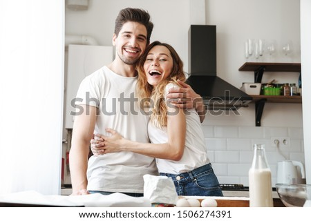 Image of caucasian young couple rejoicing while cooking breakfast together with milk and eggs in apartment