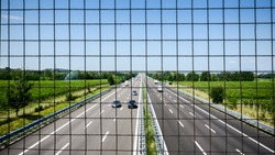 Image of chain link fence on bridge over pass. Chain fence on bridge above highway. Abstract industrial image of chain link fence and cars on highway