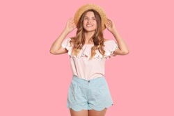 Image of charming adorable European woman touching her straw hat with both hands, looking aside, wearing blue shorts and blouse, being in high spirits, having fair hair. People and emotions concept.