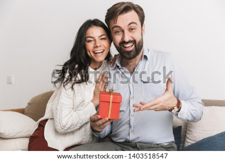 Image of charming couple man and woman holding birthday present box while sitting on sofa in bright room at home