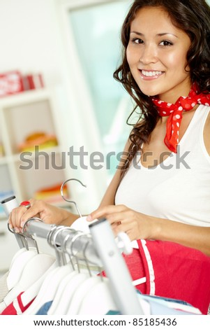 Image of charming girl choosing new clothes in clothing department