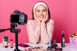 Image of charming young brunette woman advertises new beauty products, makes video her blog. Beauty vlogger sits smilling in front of camera with happy facial expression. Translation of tutorial video