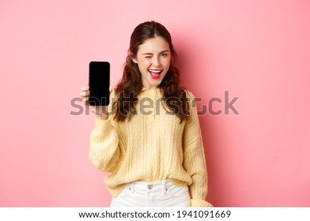Image of cheeky attractive girl, showing you smartphone screen, winking and smiling, recommending mobile phone, standing against pink background Stock photo ©