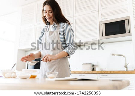 Image of cheerful brunette woman wearing apron preparing dough while cooking pie in modern kitchen stock photo