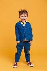 Image of cheerful excited little boy child standing isolated over yellow background. Looking aside.