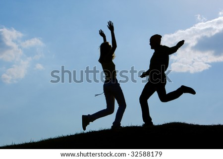 Image of cheerful girl and guy moving energetically against bright blue sky outdoors #32588179