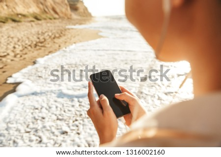 Image of cheerful girl 20s wearing earphones using mobile phone while walking by seaside #1316002160