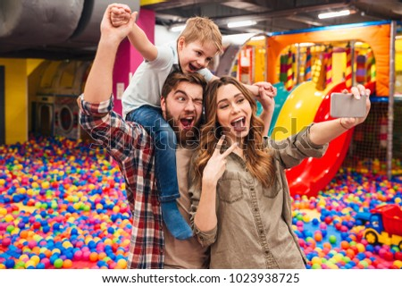 Image of cheerful little child have fun with his parents in entertainment game center. Looking aside make selfie by phone showing peace gesture.