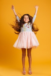 Image of cheerful little girl child jumping isolated over yellow background. Looking camera.