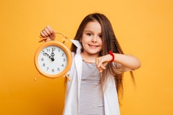 Image of cheerful little girl child standing isolated over yellow background. Looking camera pointing to clock alarm.
