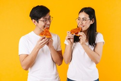 Image of cheerful multinational couple smiling and eating pizza isolated over yellow background