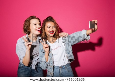 Image of cheerful two women friends standing isolated over pink background. Looking aside make selfie by phone showing peace gesture.
