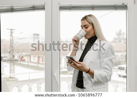 Image of cheerful young business woman in office  chatting by mobile phone and drinking coffee while standing next to the window in the office.