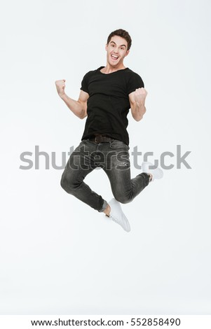Image of cheerful young man dressed in black t-shirt jumping over white background make winner gesture.