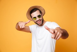 Image of cheerful young man standing isolated over yellow background. Looking at camera and pointing.