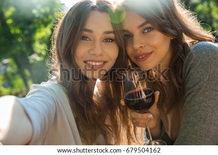 Image of cheerful young two women outdoors in park drinking wine make selfie. Looking camera.