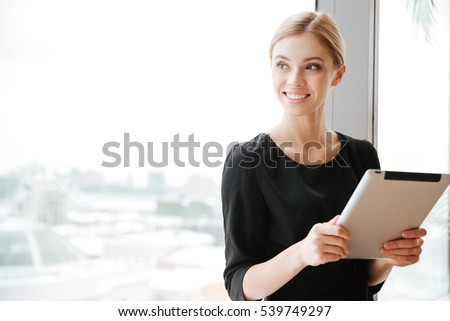 Image of cheerful young woman worker sitting in office near window while holding tablet computer. Looking aside.