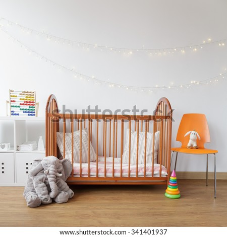 Image of child room with wooden crib and pink carpet