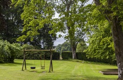 Image of childrens swing set in green park.