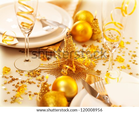 Image of Christmastime table decoration, luxury white dishware served with silver cutlery adorned with glowing glitters, golden holiday decorations, festive utensil, romance New Year dinner