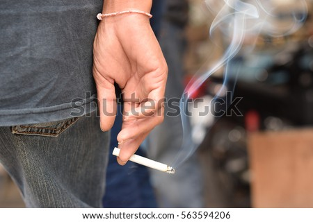 Image of cigarette in man hand with smoke.