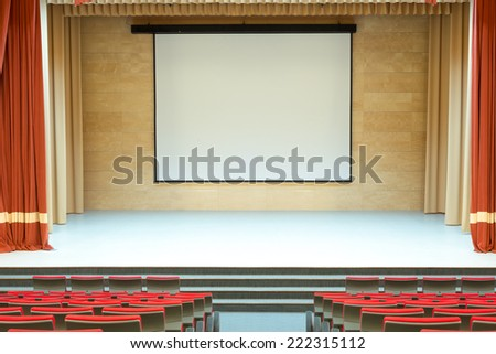 Image of cinema auditorium with blank screen and red seats