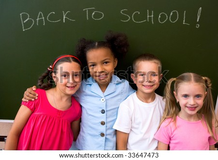 Image of clever schoolchildren standing by blackboard and looking at camera