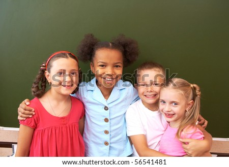Image of clever schoolchildren standing by blackboard and looking at camera - stock photo