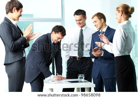 Image of co-workers congratulating their colleague while he signing paper at meeting