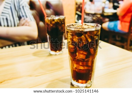 Image of cola in glass with ice cubes on the wooden table in restaurant. Vintage effect style pictures