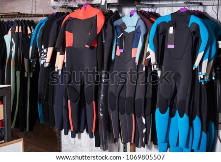 Image of colorful wetsuit hanging in the modern asian store for surfing #1069805507