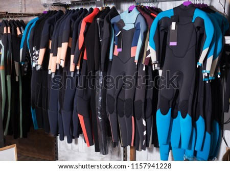 Image of colorful wetsuit hanging in the modern european store for surfing #1157941228